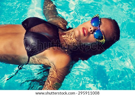 tanned young attractive woman in black bikini and sunglasses floating in pool - stock photo
