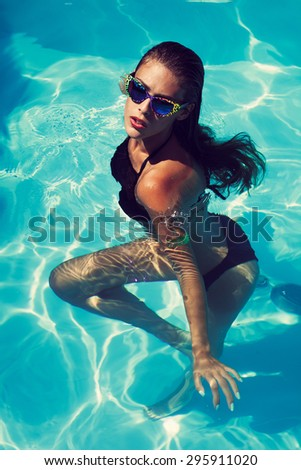 tanned young attractive woman in black bikini and sunglasses in pool - stock photo