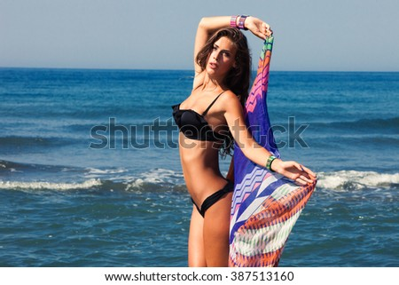 tanned young woman in bikini and colorful sarong on sea beach sunny summer day - stock photo