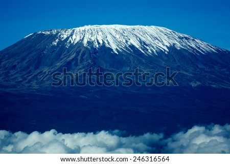 TANZANIA - DECEMBER 10, 2014: Ice cap on Mount Kilimanjaro's highest summit Uhuru.  Kibo's crater rim peak covered with white glaciers. Blue and white dominates. The bottom part is covered by clouds. - stock photo