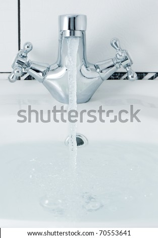 tap with a water stream. A bathroom with a white tile - stock photo