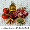 Tapas and Ingredients with Smoked Bacon, Tomatoes and Tomato Sauce, Bread Sticks, Spices and Olive Oil closeup on Wicker background - stock photo