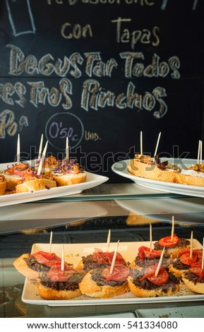 Tapas bar counter with assorted pincho tapas and a traditional chalboard in the background