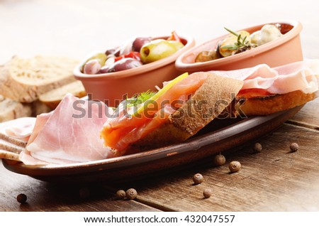 Tapas of salmon, mussels, jamon and olives on ceramic plate