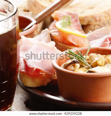 Tapas of salmon, mussels, jamon and olives on ceramic plate with glass of beer aside