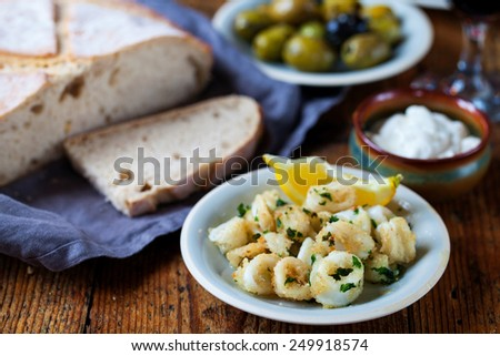 Tapas of squid, stuffed peppers and olives - stock photo