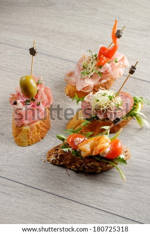 Tapas on Crusty Bread - Selection of Spanish tapas served on a sliced baguette. - stock photo
