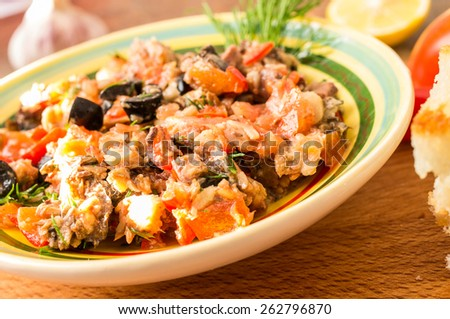 Tapas, Spanish appetizer of fish and vegetables in a bowl on a table with tomatoes and hot peppers.