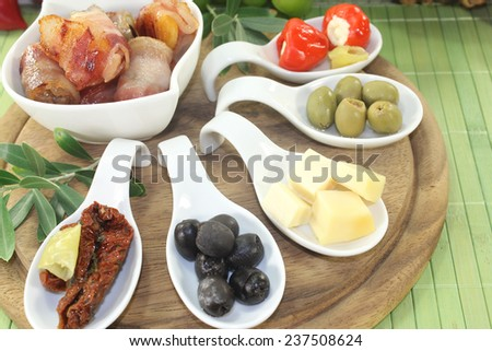 Tapas stuffed with prunes, figs, apricots and bacon on a bright background - stock photo