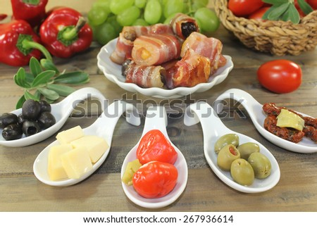 Tapas stuffed with prunes, figs, apricots and bacon on wooden background
