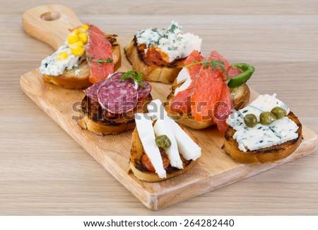 Tapas with cheese, salami, salmon, tomato and herbs - stock photo