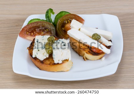 Tapas with soft blue cheese and black tomato - stock photo