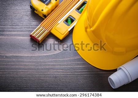 Tape-line blueprints construction level hard hat and wooden meter on vintage wood board maintenance concept. - stock photo