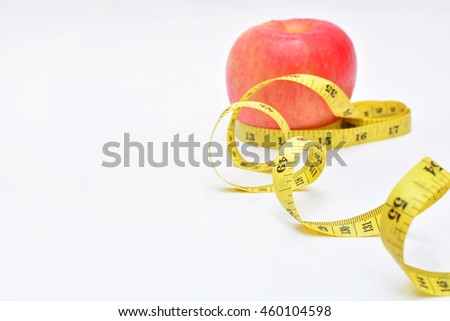 Tape measure and blurry red apple for loss weight concept