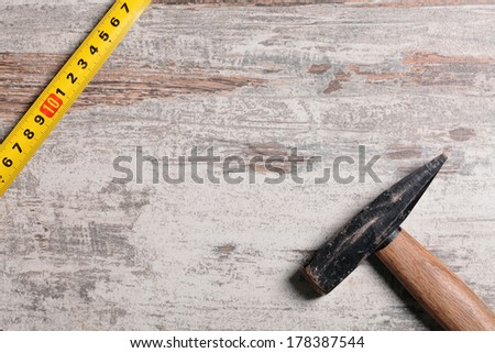 Tape measure and hammer on wooden table - stock photo
