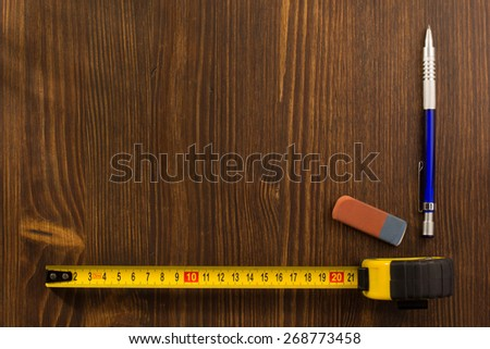 tape measure and pencil on wooden texture - stock photo