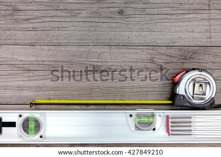 tape measure and spirit level on gray wooden boards - stock photo