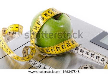 Tape measure around a green apple on a bathroom scales, isolated on white