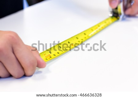 tape-measure in hand with white background
