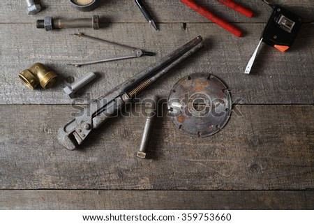 Tape-measure, internal screws, bolts, manometer, diamond wheel, pliers, pipe wrench on old wooden table. top view. copy space. - stock photo