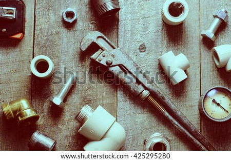 Tape-measure, internal screws, pipe screw, PVC pipe connectors, manometer on wooden background. top view. flat lay. - stock photo
