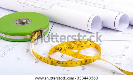 Tape measure placed on the desk, filled with building plans. In order to work in a building