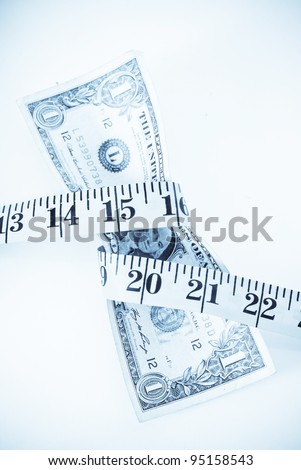Tape Measure Squeezing Dollar Bill - stock photo
