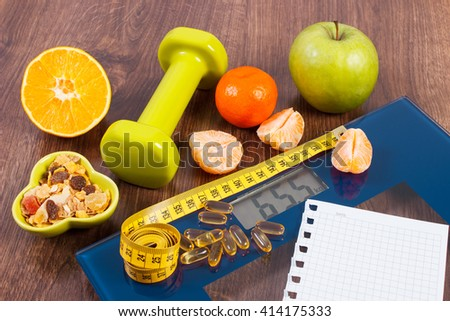 Tape measure, tablets supplements on digital bathroom scale for weight of human body, dumbbells for fitness and fresh fruits with muesli, concept of healthy lifestyle and slimming