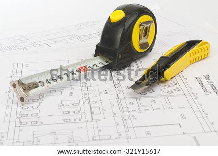 Tape measure with cutter on draft background