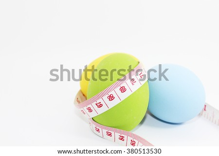 Tape measure wrapped around the Easter egg on white background,healthy concept - stock photo
