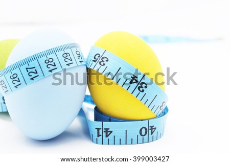 Tape measure wrapped around the Easter egg on white background,healthy concept