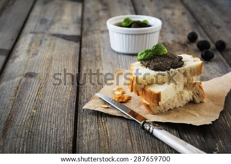 Tapenade, traditional Provence dish with olives,capers and basil on an old  wooden table background. Selective focus. - stock photo