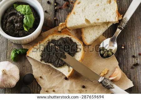 Tapenade, traditional Provence dish with olives,cracker and basil on an old  wooden table background. Selective focus. - stock photo
