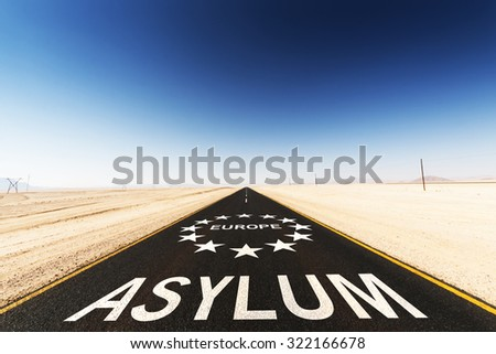 tar road in the Sahara desert with the words Asylum Europe. Social concept for the migrant crisis - stock photo