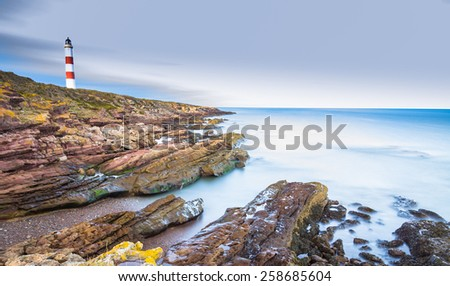Tarbat Ness cliffs with lighthouse in the distance - stock photo