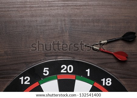 target and two darts on the brown wooden table - stock photo