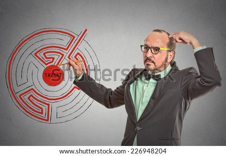 Target man labyrinth. Man drawing with pencil red path line through maze to success isolated grey wall office background. leadership guidance idea skills concept. Guy scratching head solving problem  - stock photo