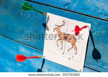 Target on a blue background. The target punctured with a dart. Accurate shooting on a target. Firing at the purpose. A target in the form of a deer.  Firing from the pneumatic weapon.  - stock photo