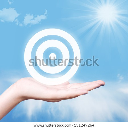 Target symbol in human hand against blue sky. Strategy concept. - stock photo