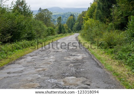 Tarmac road with big holes - stock photo