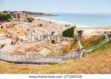 Tarragona, Spain - August 16, 2014: The Historical amphitheater of Tarragona with walking tourists, Catalonia, Spain, Mediterranean coast - stock photo