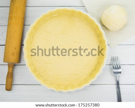 Tart dough (shortcrust pastry) in ceramic tart pan (baking form) prepared for baking - stock photo