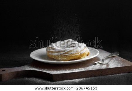 Tart with a fall of powdered sugar on wooden cutting board and black background