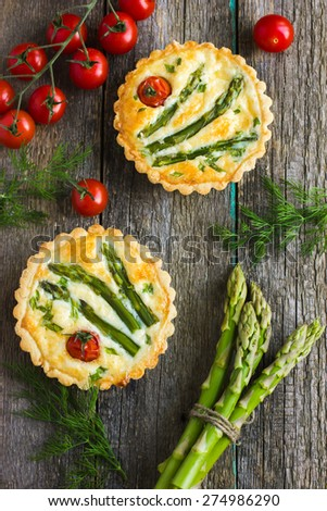 tart with asparagus and cherry tomatoes  on rustic background, top view - stock photo