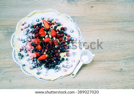 tart with berries on wooden background with space for text