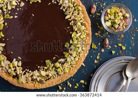 Tart with caramel, chocolate and nuts, top view - stock photo