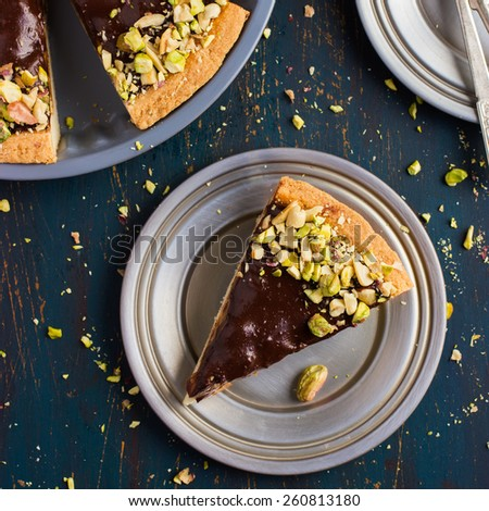 Tart with caramel, chocolate and nuts, top view, square image - stock photo