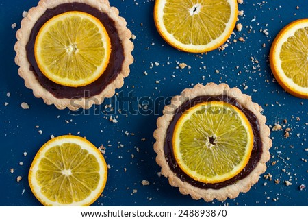 Tart with chocolate and orange on blue background, top view - stock photo