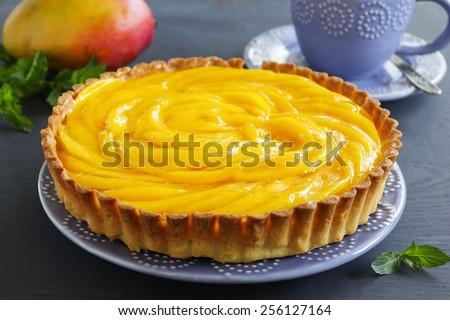 Tart with mango and raspberries. - stock photo