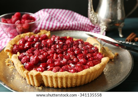 Tart with raspberries on tray, on wooden background - stock photo